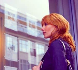 lady looking in estate agent window