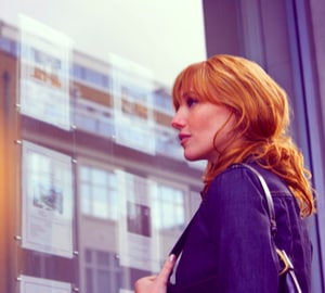 lady looking in estate agent window