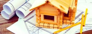 wooden model of house on drawing plans