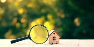magnifying glass in front of small house