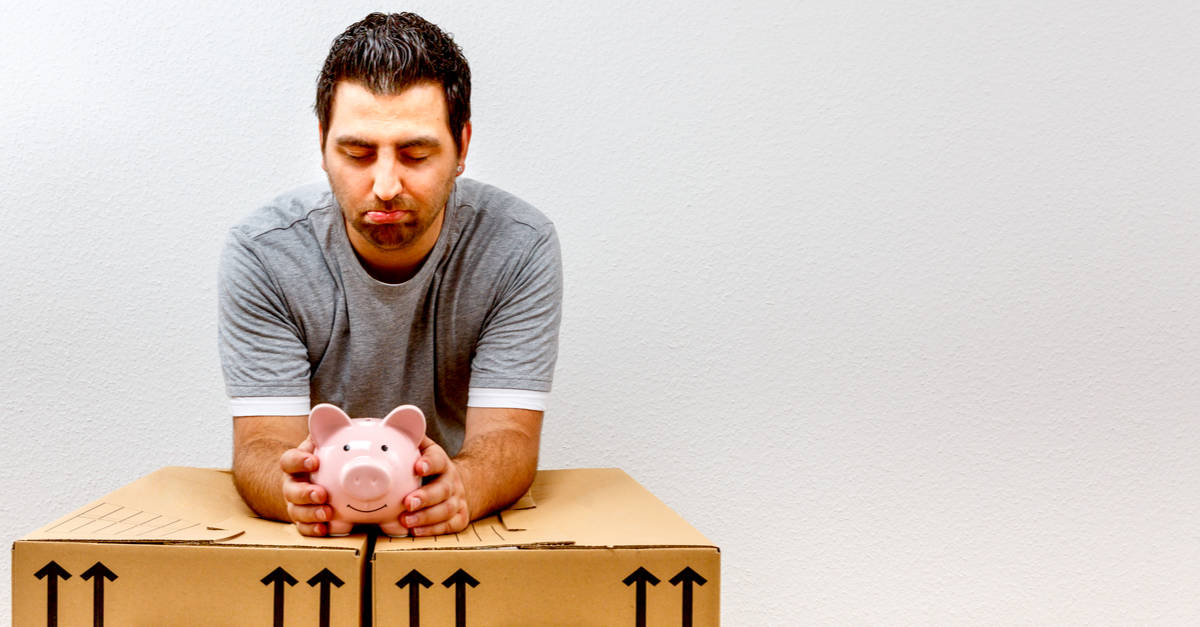 man leaning on moving boxes looking at savings