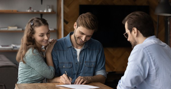 happy people signing house contract